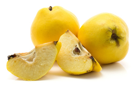 Two yellow quinces set with slices isolated on white background raw ripe