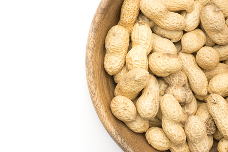 Unshelled peanuts top view in a wooden bowl isolated on white background