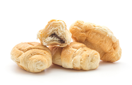 Three baked croissants or cornetto with one half filled with chocolate isolated on white background