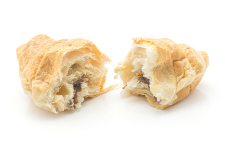 Broken baked croissant or cornetto isolated on white background two halves with chocolate cream inside Archivio Fotografico