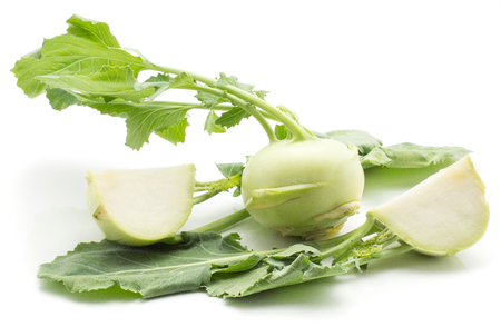 Kohlrabi (German turnip or turnip cabbage) one bulb two sliced quarters with fresh leaves isolated on white background  Stock Photo