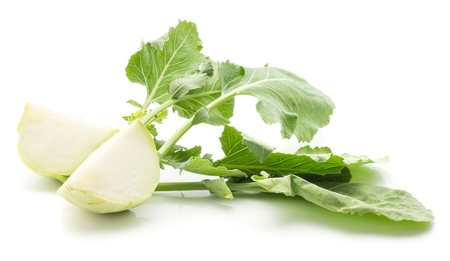 Two kohlrabi (German turnip or turnip cabbage) sliced quarters with fresh leaves isolated on white background
