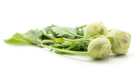 Three kohlrabi (German turnip or turnip cabbage) bulbs with fresh leaves isolated on white background raw