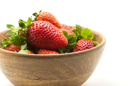 Strawberries in a wooden bowl isolated on white background