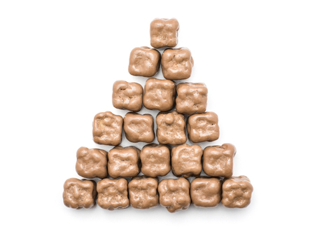 Coconut cubes in milk chocolate put together in pyramid top view isolated on white background  Standard-Bild