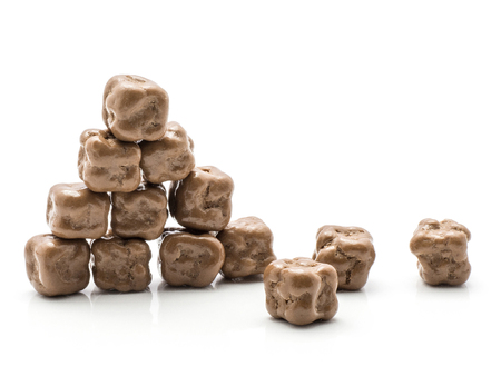 Coconut cubes in milk chocolate put together in pyramid isolated on white background
