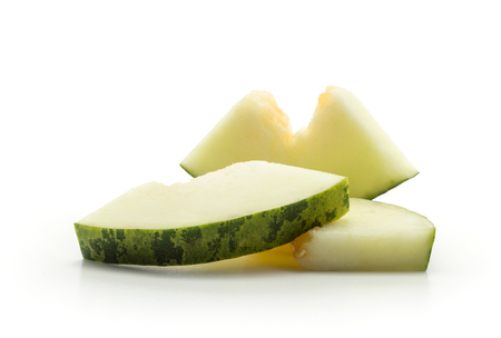 Melon Piel de Sapo three cut pieces (Santa Claus Christmas variety) isolated on white background without seeds