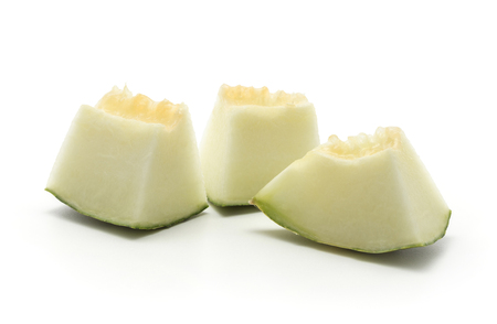Three melon Piel de Sapo pieces (Santa Claus Christmas variety) isolated on white background green striped outer rind