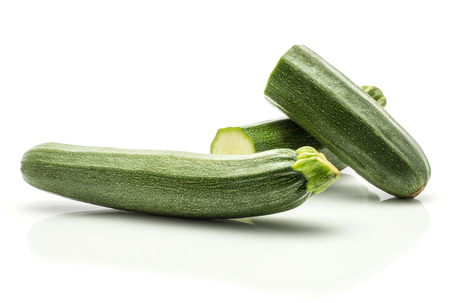 One green zucchini and two sliced halves isolated on white background long raw courgette