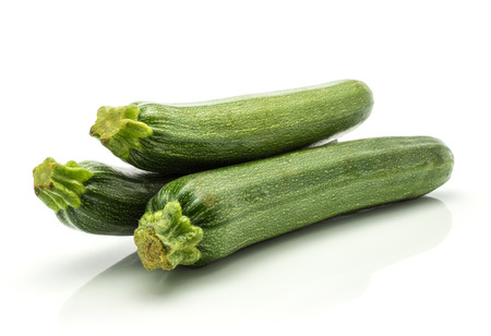 Three green zucchini isolated on white background long raw courgette Foto de archivo
