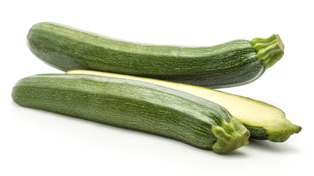 Sliced green zucchini and one whole isolated on white background long raw courgette and two section halves