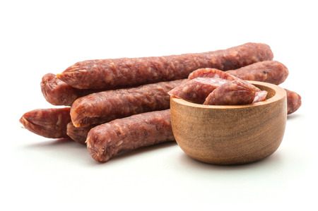 Hungarian dry sausages pepperoni pieces in a wooden bowl with separated stack isolated on white background smoked in natural casing mixed pork and beef