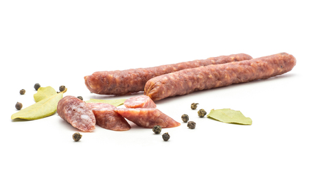Two Hungarian dry sausages pepperoni with black pepper bay leaves and cut pieces isolated on white background smoked in natural casing mixed pork and beef