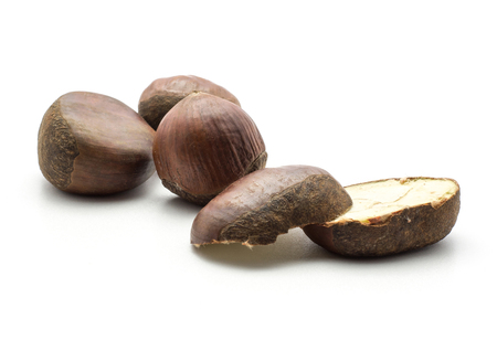 Three European chestnuts two halves Spanish edible isolated on white background raw fresh brown nuts