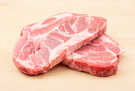 Raw pork neck meat cuts isolated on wood background fresh two slices without bone