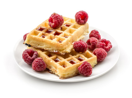 Traditional waffle (Belgian) with fresh raspberries on a saucer and honey isolated on white background two sweet delicate and airy delicious breakfast