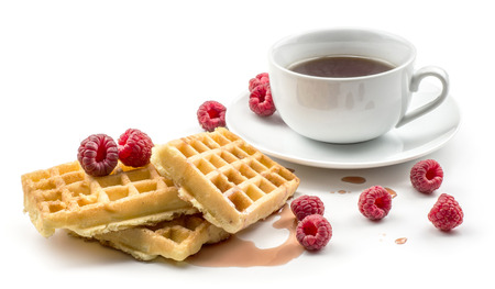 Traditional waffle (Belgian) with fresh red raspberries syrup and cup of tea isolated on white background three sweet delicate and airy delicious breakfast
