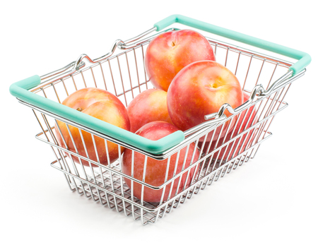 Plums red orange in a shopping basket isolated on white background ripe and fresh