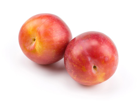Two plums red orange isolated on white background fresh and glossy