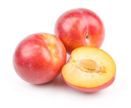 Pruimen rode sinaasappel twee gehele half geïsoleerd op witte vers en glanzend achtergrond Stockfoto