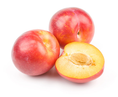 Plums red orange two whole one half isolated on white background fresh and glossy