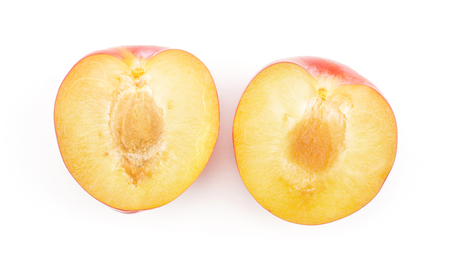 Plums red orange two sliced halves top view isolated on white background  Stock Photo