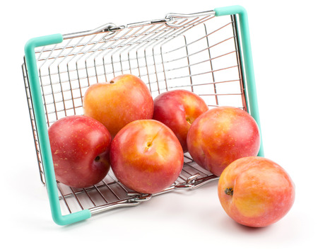 Plums red orange out a shopping basket isolated on white background  Stock Photo