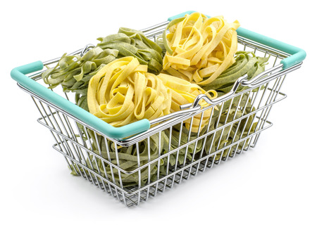 Fettuccine pasta in a shopping basket raw spinach and classic isolated on white background