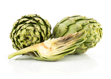 Two globe artichoke heads and one slice isolated on white background fresh cut raw