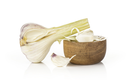 Young garlic one bulb and separated cloves in a wooden bowl isolated on white background