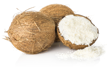 Two coconuts and one broken half filled with shavings isolated on white background brown fibrous shell with milk meat  Stock Photo