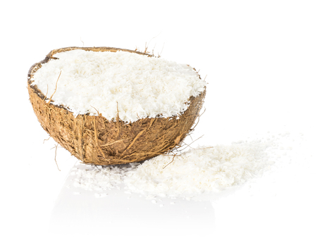 One coconut half filled with shavings isolated on white background brown fibrous shell with milk meat