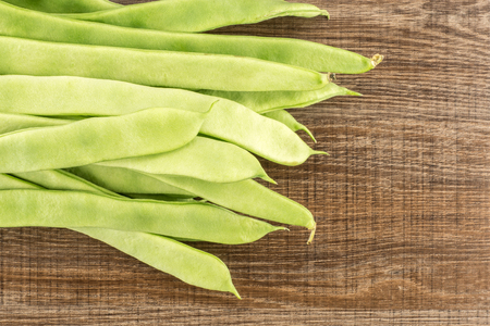 Flat green beans top view isolated on wooden background long