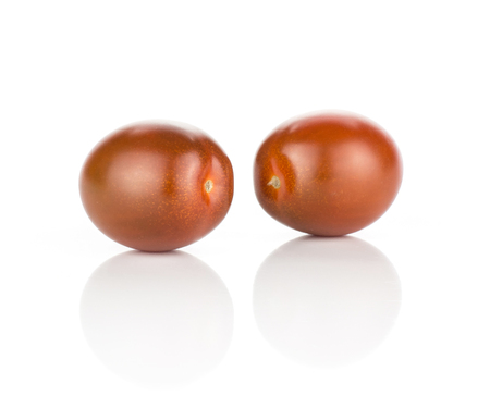 Two black red grape cherry tomatoes isolated on white background