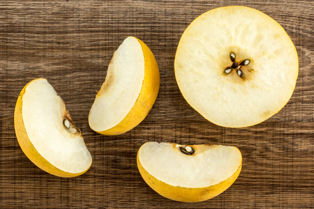 Chinese golden pears top view Nashi variety isolated on wooden background one half three slices