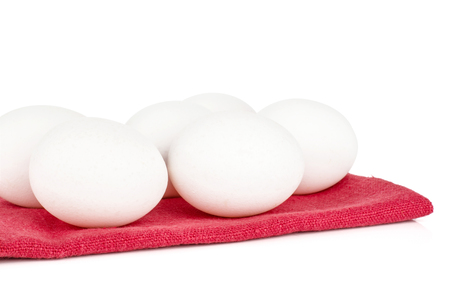 White chicken eggs on a red textil blanket isolated on white background