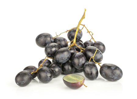 Black grape cluster (autumn royal variety) with one sliced half isolated on white background