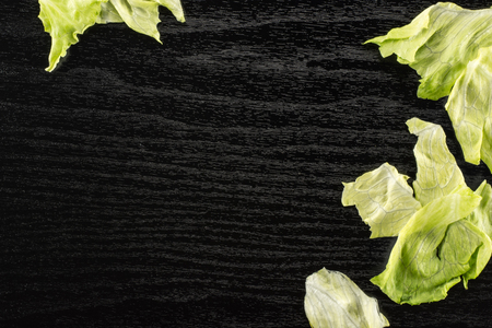 Iceberg lettuce table top isolated on black wooden background fresh torn salad leaves stack
