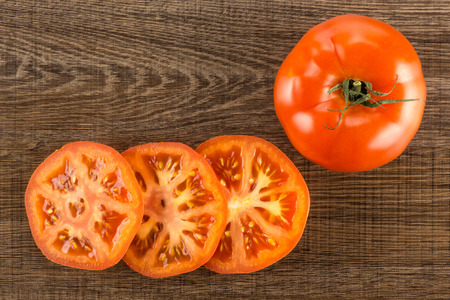 One red tomato and three slices top view isolated on brown wood background