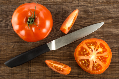 Red tomato composition with a knife isolated on brown wood background top view one whole one section half and two slices