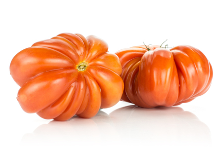 Two beef tomatoes (flower shape) isolated on white background big ripe red ribbing