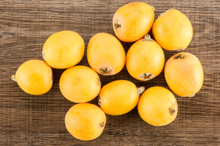 Fresh orange Japanese loquats top view isolated on brown wood background  Stock Photo