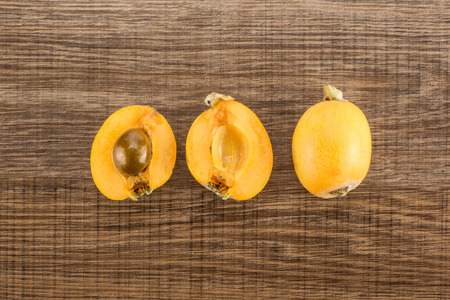 Fresh orange Japanese loquats collection top view isolated on brown wood background one cut in two halves with a seed and whole