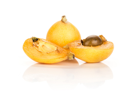 Fresh orange Japanese loquat and one cut in two halves with a seed isolated on white background  Imagens