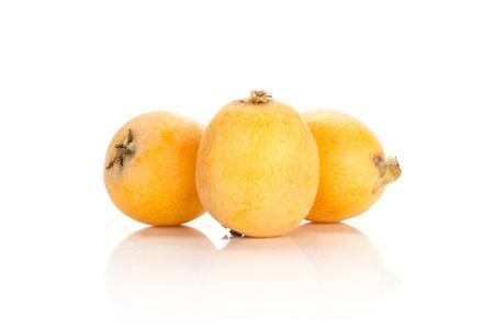 Group of three fresh orange Japanese loquats isolated on white background