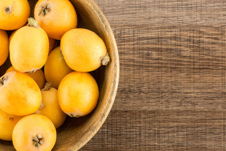 Fresh orange Japanese loquats in a wooden bowl flatlay isolated on brown wood background