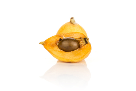 One orange Japanese loquat and section half with a seed isolated on white background  Imagens
