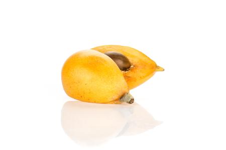 One sliced orange Japanese loquat isolated on white background two halves  Imagens