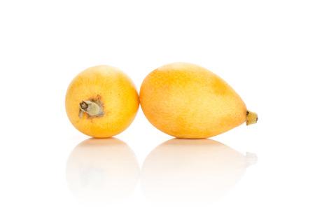 Two fresh yellow orange Japanese loquats isolated on white background