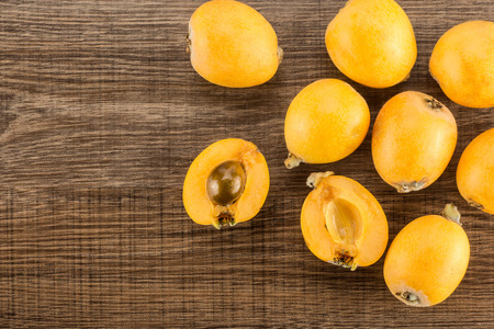 Fresh orange Japanese loquats one cut in two halves flatlay isolated on brown wood background  Imagens